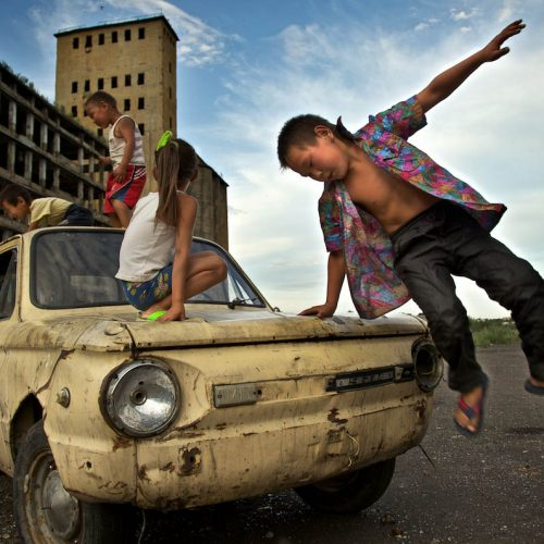 Children play on a beaten Lada outside derelict factory in Tuva