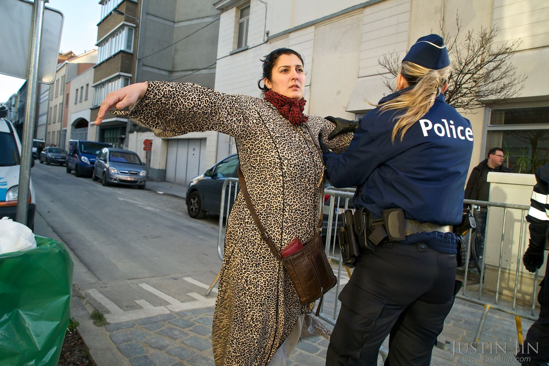 A woman is searched in Molenbeek, Brussels, on her way to a demonstration for peace.