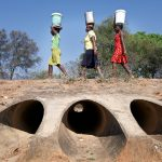 Three Zimbabwean women carry 20-litre buckets of water walk four kilometres to their homes from the nearest borehole, the area's only remaining source of water. They have to walk back and forth a total of 12 km a day to fetch water. A water way beneath them run dry. Drought in southern Africa is devastating communities in Zimbabwe, leaving 4 million people urgently in need of food aid. The government declared a state of emergency,. Here in Masvingo Province, the country's hardest hit province, vegetation has wilted, livestock is dying, and people are at serious risk of famine. Pictures shot by Justin Jin