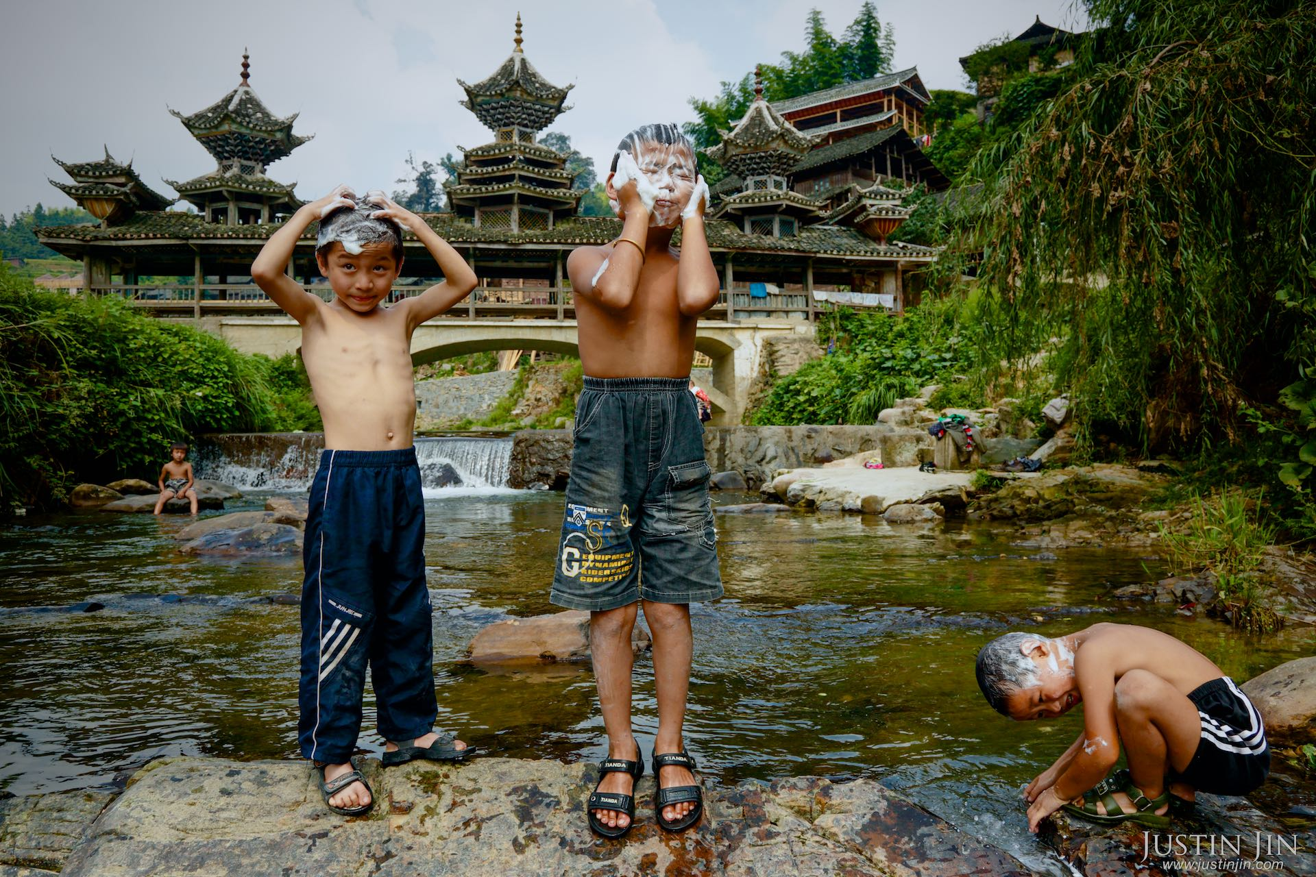 "Children bathe in the river that curves through Dimen, crisscrossed by wooden Flower Bridges. In Dong language, Dimen means, ""a place with endless spring water."""