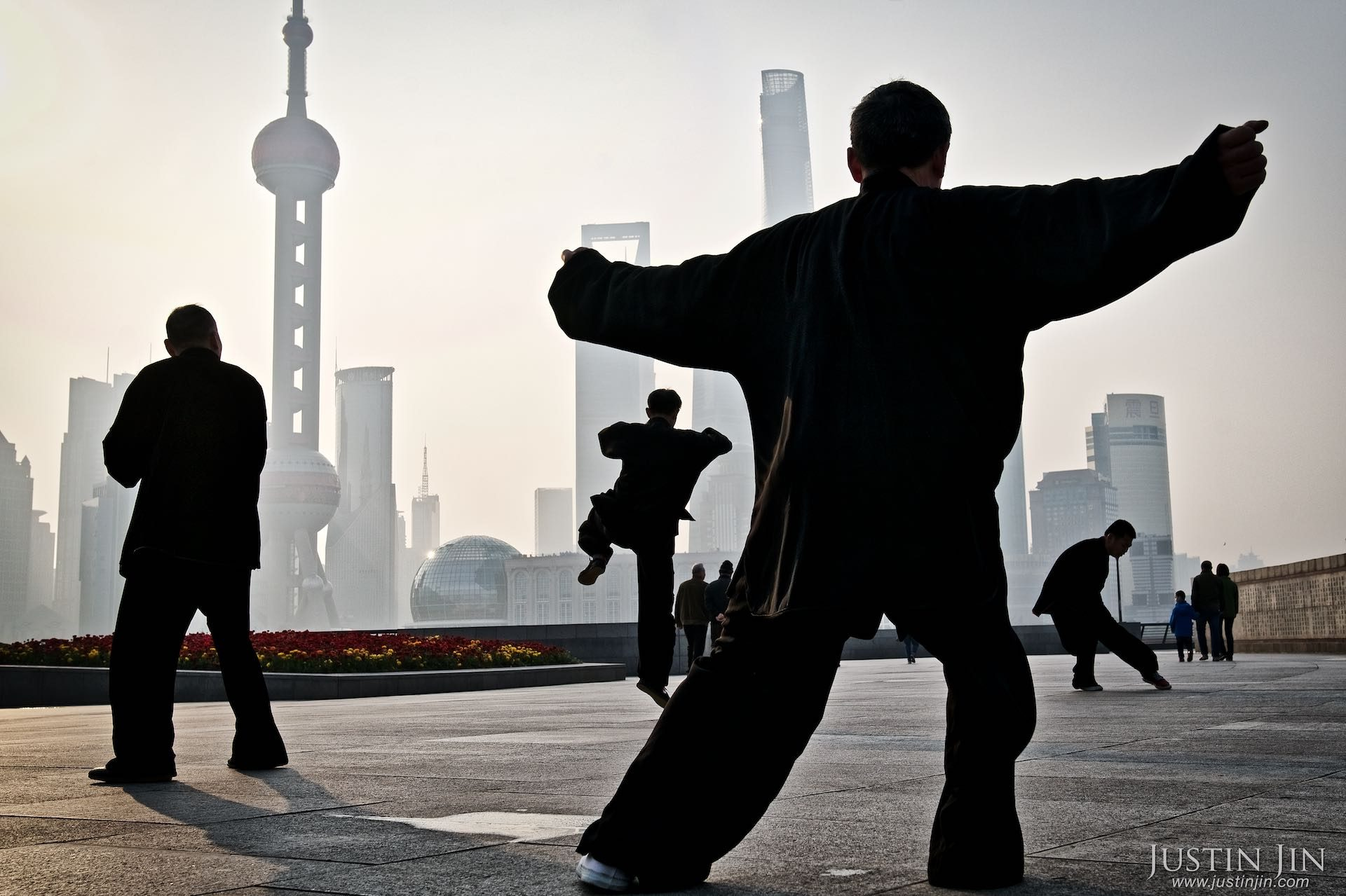 Early-risers practise tai-chi in front of the Pudong financial district, the earliest example of China's planned urbanization.